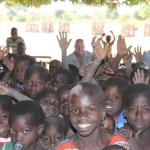 """Ieder jaar reist een delegatie vanuit het bestuur naar Ghana om de voortgang van projecten te volgen. Bij deze bezoeken worden alle dorpen aangedaan waar GMS projecten heeft. Vaak worden op zulke momenten de lessen toch even onderbroken en verzamelen de leerkrachten en de kinderen zich op het schoolplein. In de schaduw, onder een mango-tree wordt het GMS-bestuur dan geinformeerd over de voortgang van het onderwijs. De kinderen trakteren de gasten dan op een mooi lied of een net ingestuurd een toneelstukje.  De kinderen (hier van de school in Zugpeni) verdringen zich om op de foto te mogen. Op de achtergrond zien we enkele jonge mannen die als hulponderwijzer op school werkzaam zijn.  De blanke """"kaaskop"""" in het midden is Ad v.d. Bom die Jan de Rijke januari 2012 vergezelde."""