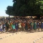 """Tijdens de jaarlijkse bezoeken aan het gebied, bezoekt het bestuur alle omliggende dorpen van Yikpabongo. Ondertussen bestaan ook met de scholen in de andere dorpen goede samenwerkingsrelaties.  In de dorpen gaan de kinderen naar de primary school. Dit  is vergelijkbaar met onze basisschool. In de omgeving is dikwijls nog wel een aanbod van verlengd basis onderwijs, Junior Highschool. Maar voor vervolgonderwijs, Senior High School (VMBO, MAVO, HAVO e.d.) zijn de kinderen toch aangewezen op scholen buiten het gebied.  Op de foto zwaaien de kinderen van de school uit Tuvuu ons hartelijk uit. Bij iedere school is er een of meer bomen geplant die verkoeling brengt tijdens een """"meeting"""" .  Het gebrek aan klaslokalen wordt dikwijls praktisch opgelost. De jongsten krijgen les in de open lucht: onder de bomen worden dan houten schoolbankjes neergezet, waar de kinderen soms met 3 tegelijk in zitten. Gewoon een kwestie van makke schapen.  De kinderen hebben doorgaans schooluniformen aan.  Zo zien we op de foto, op de achtergrond wat opgeschoten jongens en meisjes in blauwe tenues. De allerjongsten hebben dikwijls nog hun gewone kleertjes aan.  Soms mogen ook peuters een dagje met hun oudere broertje of zusje mee naar school.   Het schoolplein is gemarkeerd met keien. Op het schoolplein wordt na schooltijd vaak gevoetbald en gespeeld."""